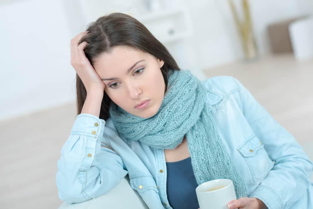 Eine traurige Frau mit einem Schal um den Hals sitzt und denkt über Kaffee nach