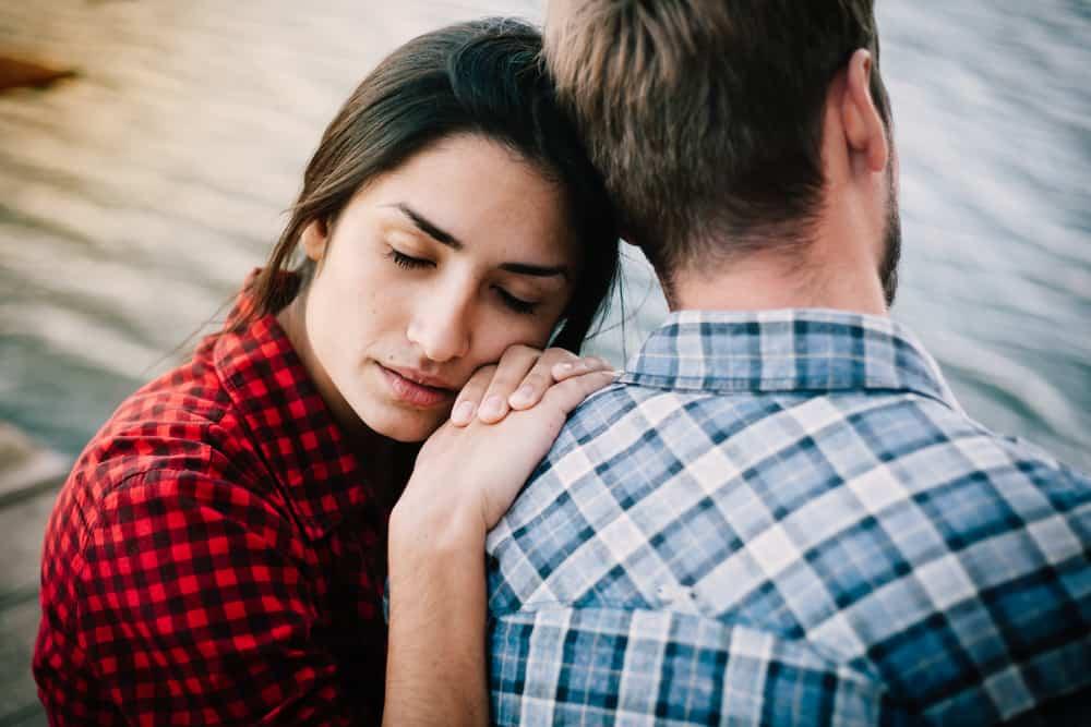 Eine traurige Frau stützte sich auf die Schulter ihres Mannes