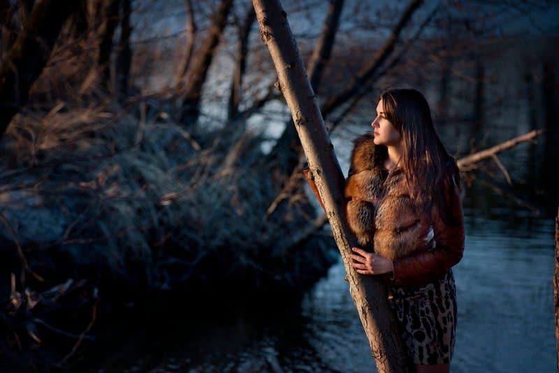 Eine traurige Frau steht an einem Baum und schaut weg