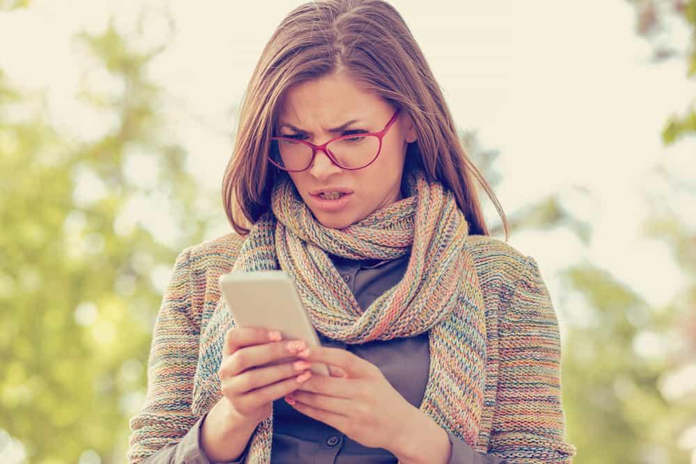 Eine wütende Frau mit Brille steht draußen und liest eine SMS