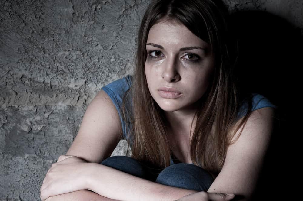 Eine weinende Frau sitzt zusammengerollt im Dunkeln auf dem Boden