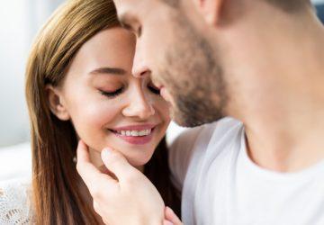 Ein Mann mit Bart umarmt eine attraktive lächelnde Brünette