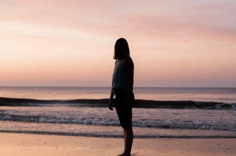 ein einsames Mädchen am Strand stehen