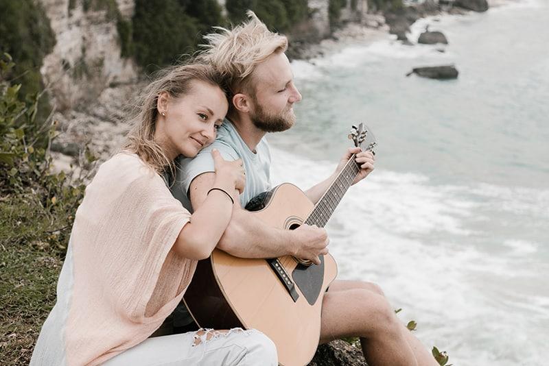 Eine Frau umarmt ihren Mann von hinten, während er auf den Felsen in der Nähe des Meeres Gitarre spielt