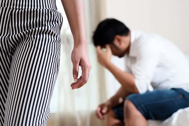 Frau, die von einem Ehemann weggeht, der auf einer Couch sitzt