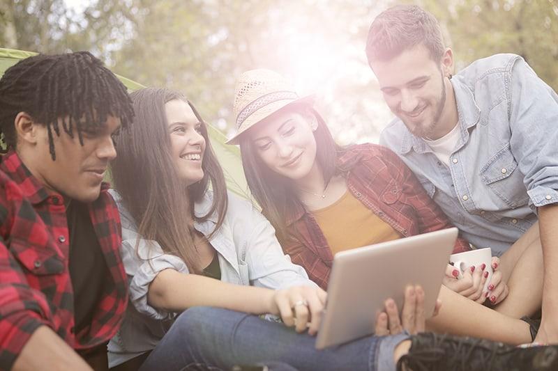 Freunde sitzen auf dem Boden und betrachten Tablette, während lächelndes Mädchen den Freund ihrer Freundin betrachtet