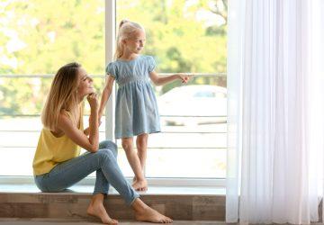 Eine junge Mutter mit ihrer Tochter schaut aus dem Fenster