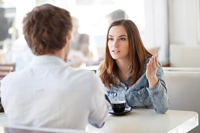 Junges Paar, das in einem Café argumentiert, während Frau mit ihren Händen gestikuliert