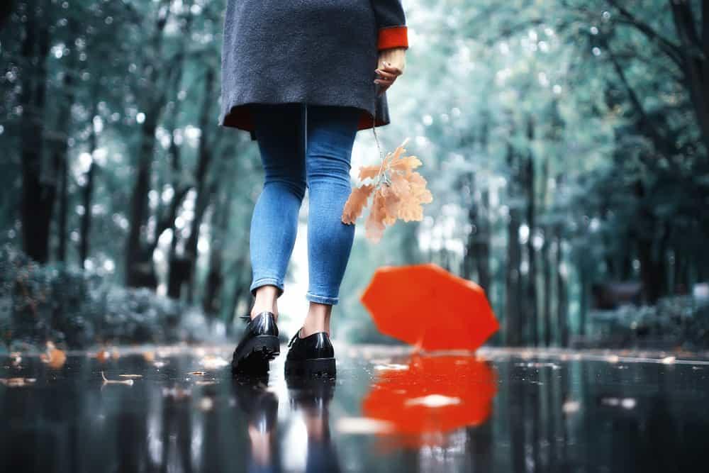 Konzentrieren Sie die Beine eines Mädchens in Schuhen, die im Regen laufen