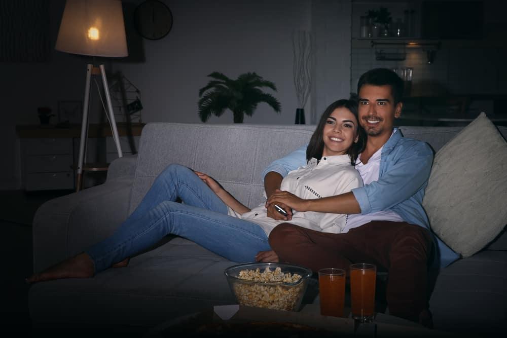 Liebespaar in einer Umarmung vor dem Fernseher