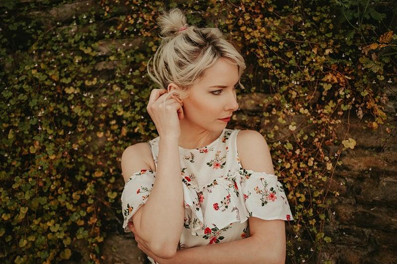 eine nachdenkliche Frau, die beiseite schaut, während sie in der Nähe von Pflanzen steht