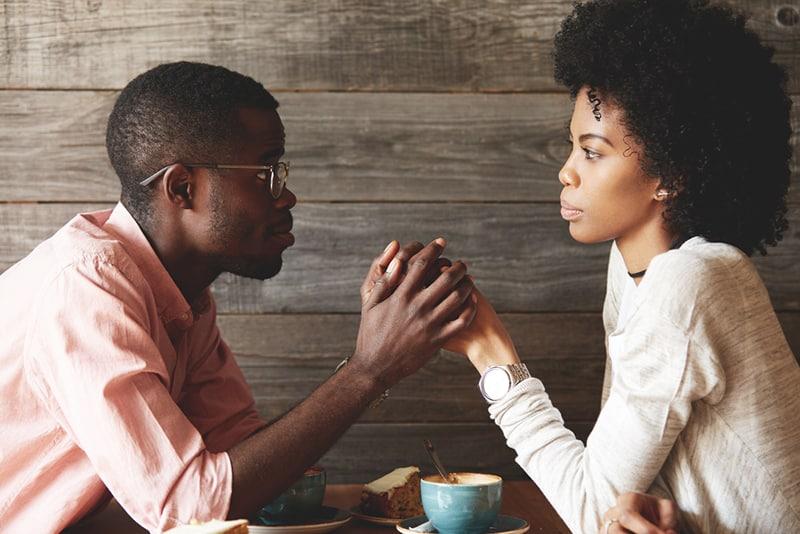 Mann in Brille hält die Hände seiner Frau, während sie verärgert aussieht