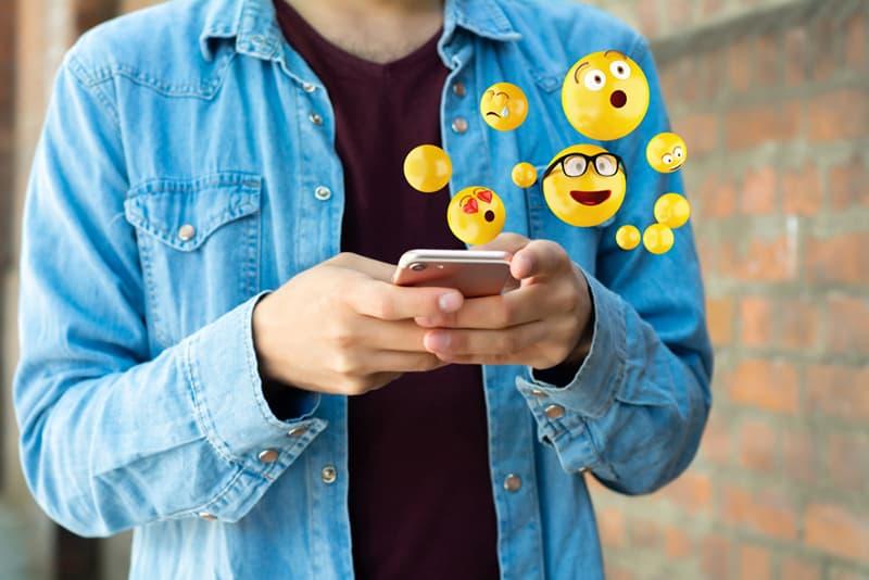 Mann mit Smartphone und Emojis senden, während in der Nähe der Wand stehen