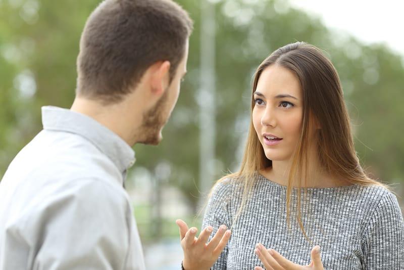 Paar, das draußen in einem Park spricht, während Frau überrascht schaut