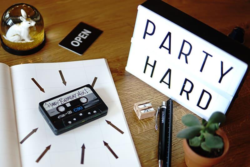 """Tonband auf Notebook und Leuchtkasten daneben mit der Meldung """"Party hard"""""""