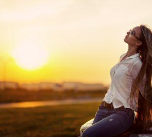Ein hübsches Mädchen genießt den Sonnenuntergang, während es im Auto sitzt