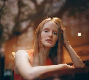 Das rothaarige Mädchen sitzt und denkt nach