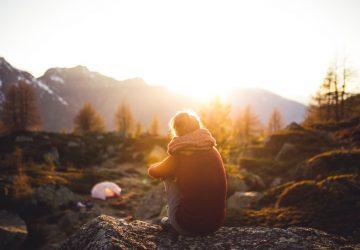 Eine Frau mit einem Schal sitzt auf einem Felsen und beobachtet den Sonnenuntergang
