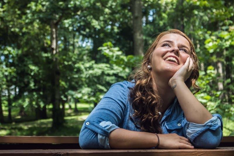 Eine lächelnde Frau sitzt auf einer Bank im Wald und denkt nach