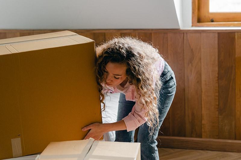 Eine Frau packt Sachen in Kisten im Schlafzimmer