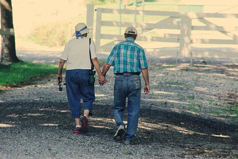 altes Ehepaar Händchen haltend beim Gehen auf der Straße