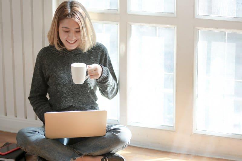 blonde Frau sitzt auf dem Boden, trinkt Kaffee und tippt auf Laptop