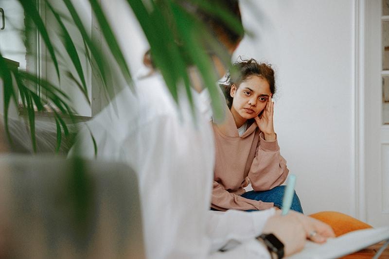 depressive Frau, die einem Therapeuten beim Sitzen auf dem Sofa zuhört