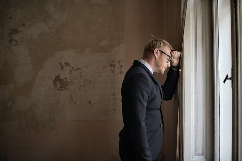 Ein verwirrter Mann, der sich an das Fenster im Gebäude lehnte