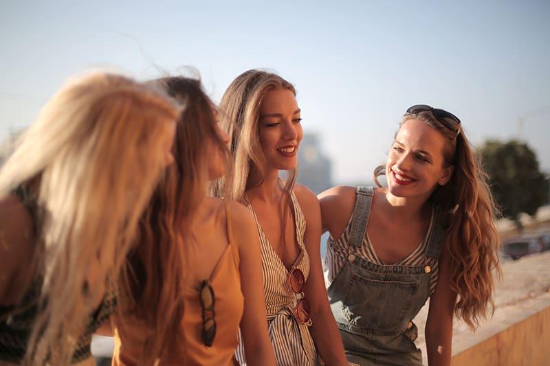drei Freundinnen, die versuchen, eine Frau aufzumuntern, die eine Bluse mit schwarzen weißen Streifen trägt, während sie draußen stehen
