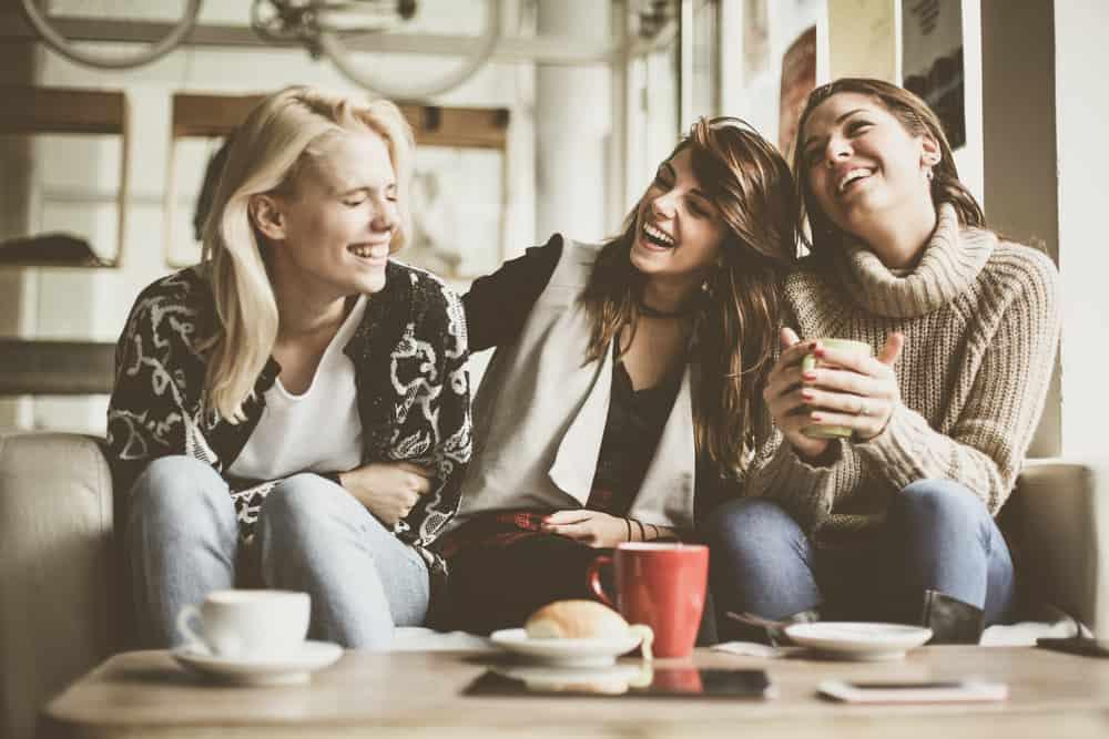 drei lächelnde Freunde, die zu Hause Kaffee trinken