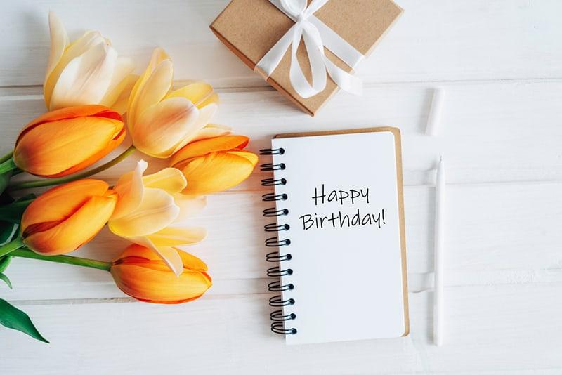 """ein """"alles Gute zum Geburtstag"""" -Text im Notizbuch in der Nähe des Blumenstraußes"""