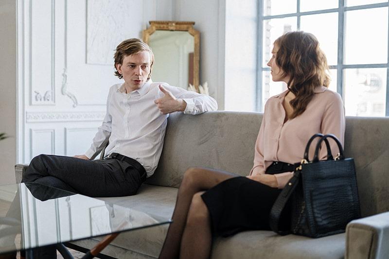 Ein Ehemann spricht mit seiner Frau, während er zusammen auf dem Sofa sitzt