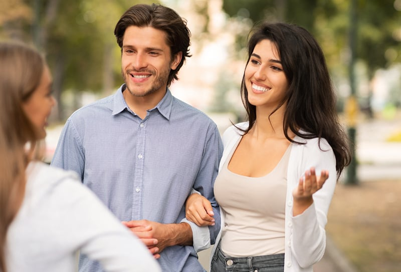 ein Mädchen, das mit einem verheirateten Paar spricht, während es auf dem Bürgersteig steht