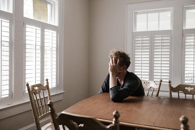 Ein Mann, der sich auf einen Holztisch stützt, während er alleine im Esszimmer sitzt