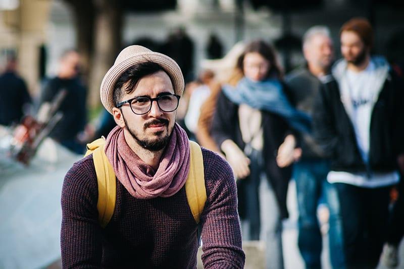 Ein Mann, der allein an einem öffentlichen Ort steht und geradeaus schaut