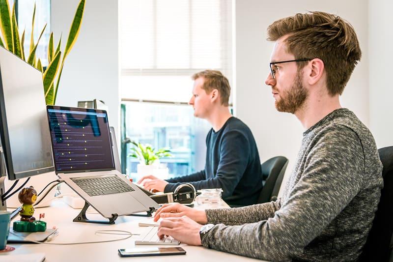 Ein Mann, der am Computer arbeitet, während er im Büro sitzt