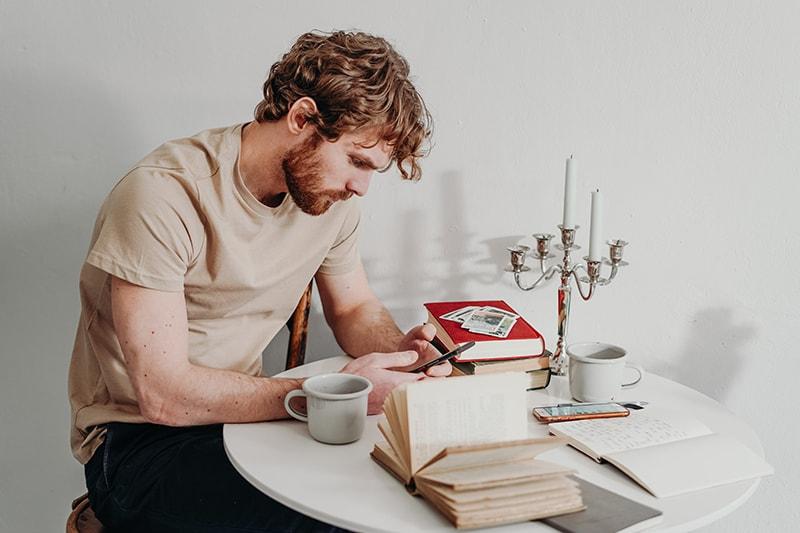 Ein Mann, der auf einem Smartphone tippt, während er am Tisch sitzt