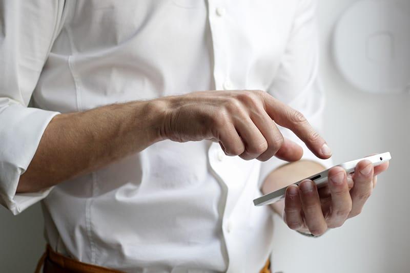 ein Mann, der auf seinem Smartphone tippt während des Stehens