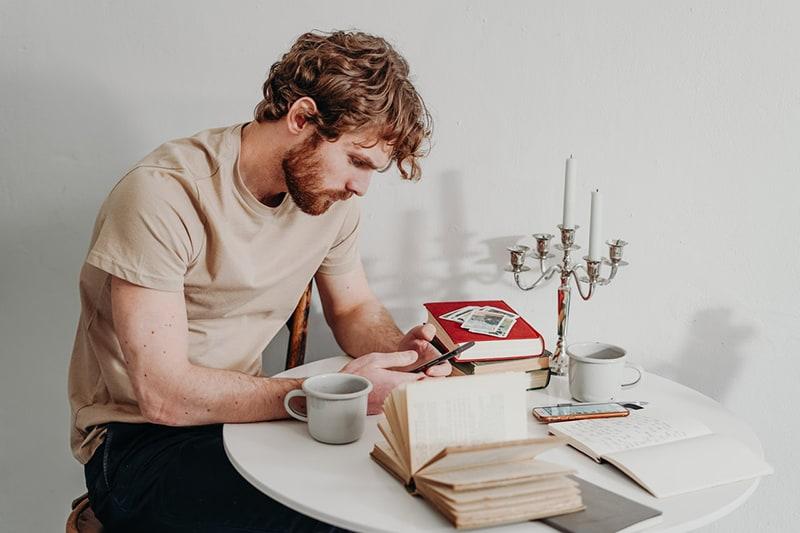 ein Mann, der eine Textnachricht auf dem Smartphone schreibt, während er am Tisch sitzt