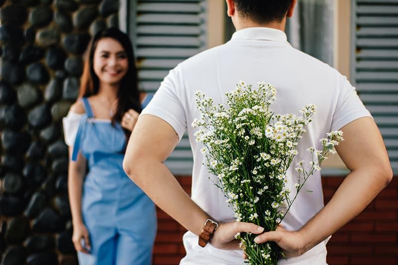 Ein Mann hält einen Blumenstrauß hinter dem Rücken, während er vor einer Frau steht