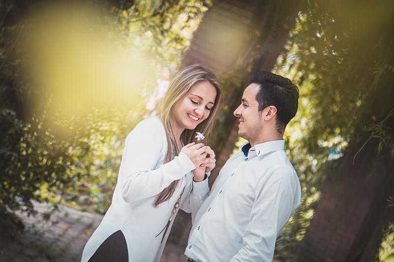 Ein Mann, der einer lächelnden Frau eine Blume gibt, während er in der Nähe von Bäumen steht