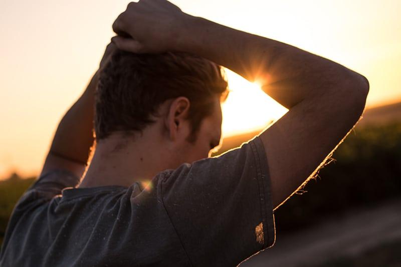 ein Mann, der seine Haare hält, während er während des Sonnenuntergangs allein steht