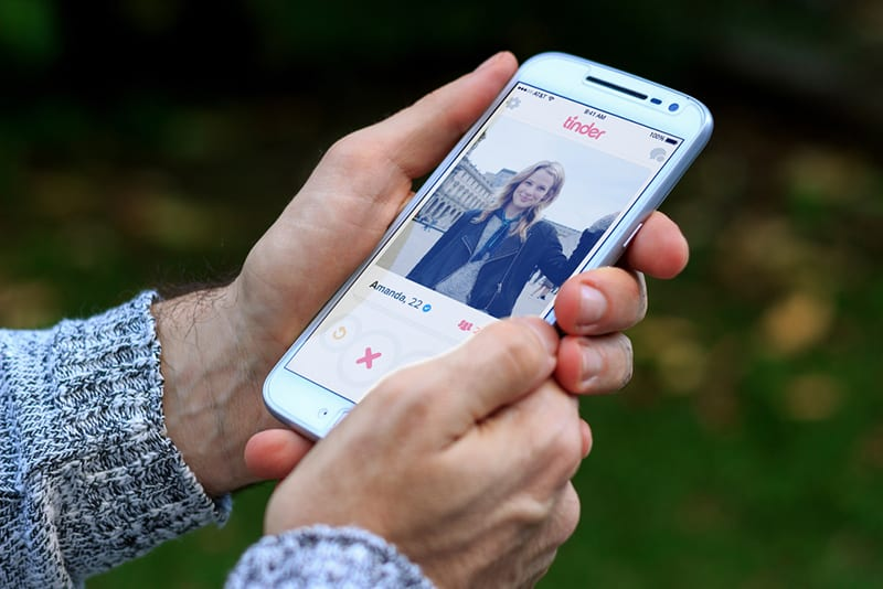Ein Mann hält ein Smartphone und benutzt Tinder mit einem geöffneten Mädchenprofil