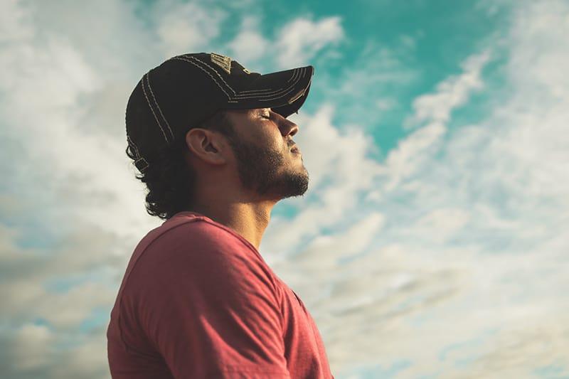 ein Mann, der eine schwarze Mütze mit geschlossenen Augen unter einem bewölkten Himmel trägt