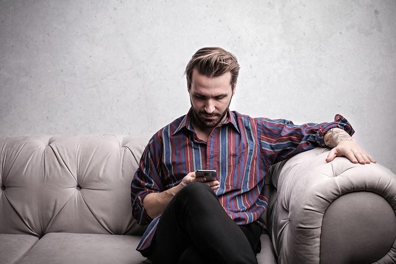 Ein Mann sitzt auf der Couch und liest eine Nachricht von einem Smartphone