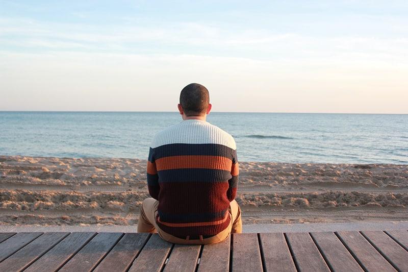 Ein Mann sitzt allein auf einer Holztafel und blickt auf den Ozean