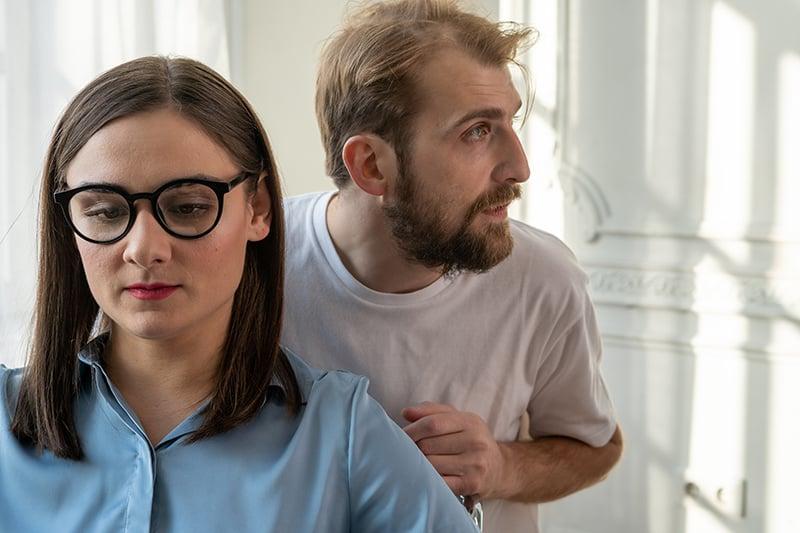 Ein Mann steht hinter einer Frau, während sie auf dem Stuhl sitzt