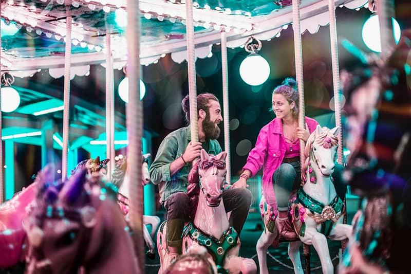 ein Mann und eine Frau, die Hände halten, während sie ein Karussell fahren