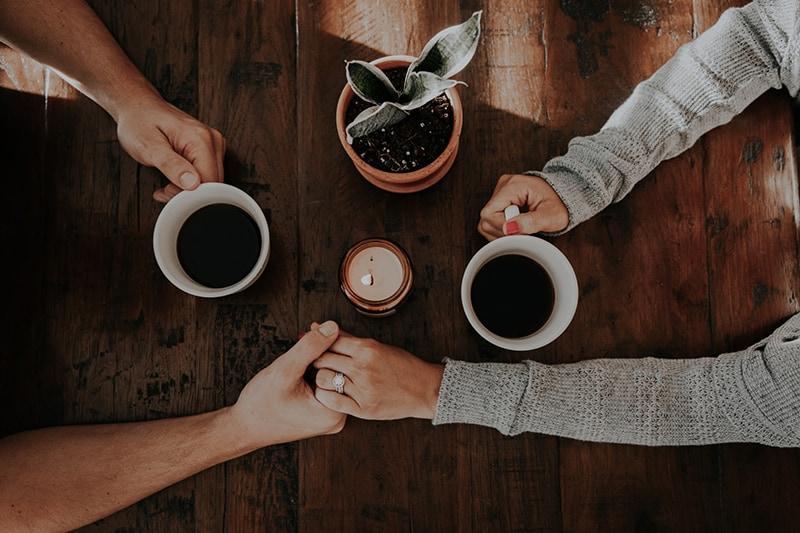 Ein Mann und eine Frau halten sich an den Händen, während sie gemeinsam Kaffee trinken