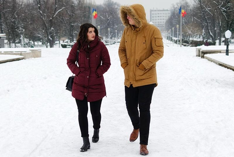 Ein Mann und eine Frau unterhalten sich beim Gehen auf dem Schnee